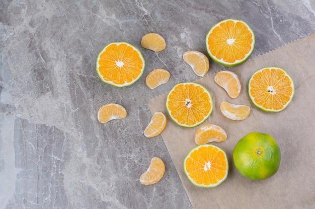 Frutas cítricas espalhadas no fundo de pedra. Foto gratuita