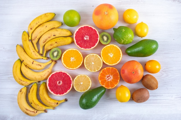 Frutas cítricas na mesa de madeira branca laranja toranja limão limão banana tangerina vista superior Foto gratuita