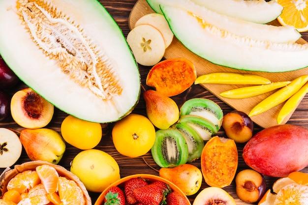 Frutas coloridas orgânicas frescas na mesa de madeira Foto gratuita