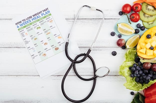 Frutas com perder peso plano e estetoscópio Foto gratuita