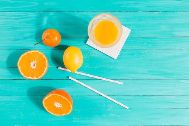 Frutas, copo de suco e palhas na mesa Foto gratuita