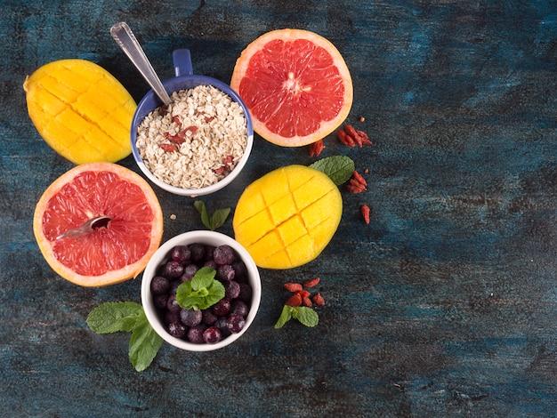 Frutas diferentes com aveia na mesa azul Foto gratuita
