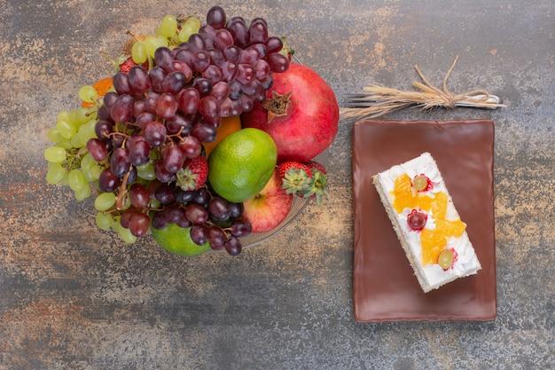 Frutas doces diferentes em prato de vidro com um pedaço de bolo em prato escuro Foto gratuita