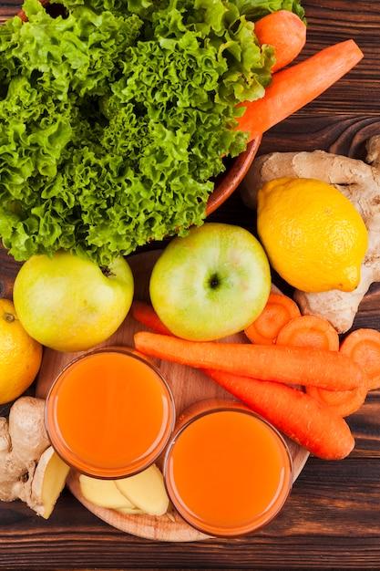 Frutas e legumes frescos com suco na mesa Foto gratuita