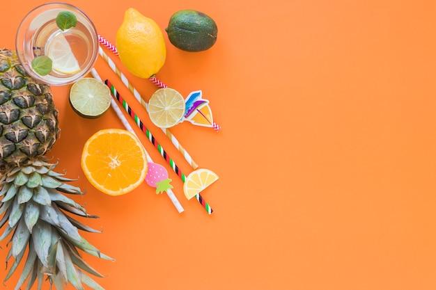 Frutas exóticas com coquetel e canudos de plástico Foto gratuita