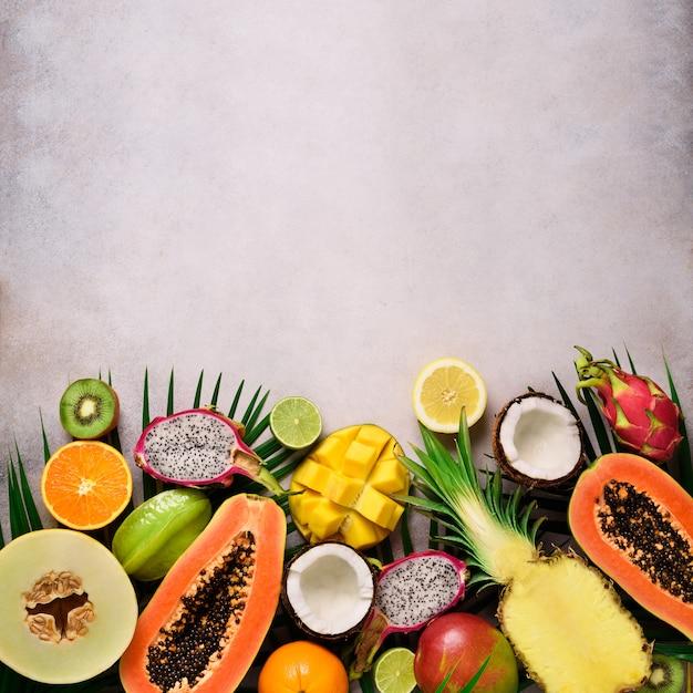 Frutas exóticas e folhas de palmeira tropicais - mamão, manga, abacaxi, banana, carambola, fruta do dragão, kiwi, limão, laranja, melão, coco, limão. Foto Premium