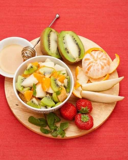Frutas frescas. ainda vida. um conjunto de frutas e uma salada de frutas e mel na placa de madeira, Foto Premium