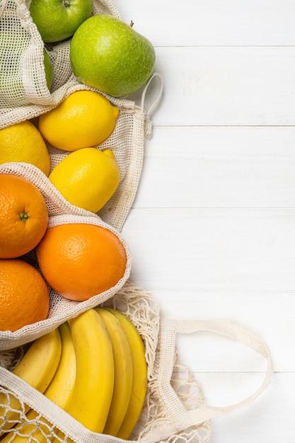 Frutas frescas, maçãs, bananas, laranjas e limões em bolsas ecológicas Foto Premium