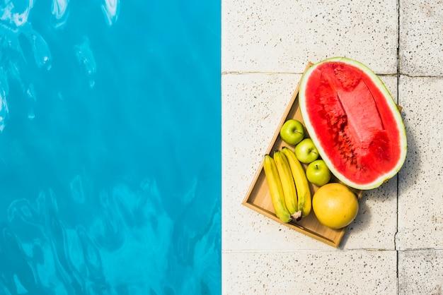 Frutas na bandeja colocada na borda da piscina Foto gratuita