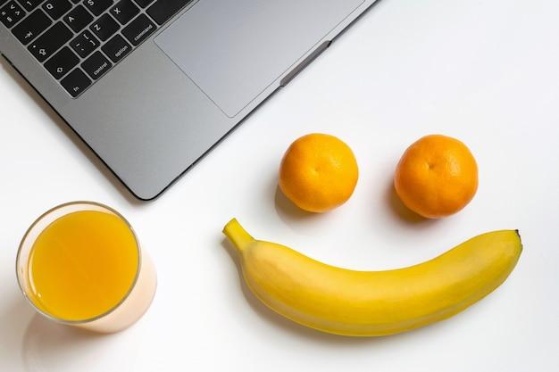 Frutas no local de trabalho. carinha engraçada. laptop, banana, mandarinas e suco de laranja Foto Premium
