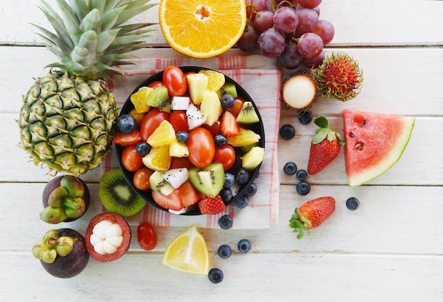 Frutas, salada, tigela, fresco, verão, frutas legumes, saudável, morangos, laranja, kiwi, mirtilos, dragão, fruta, tropicais, uva, tomate, limão, rambutan, mangosteen, abacaxi, melancia Foto Premium