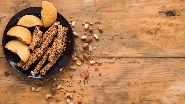 Frutas secas; cookies e barra de granola no plano de fundo texturizado de madeira Foto gratuita