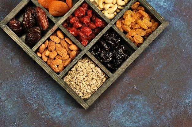 Frutas secas e castanhas em uma caixa de madeira Foto Premium
