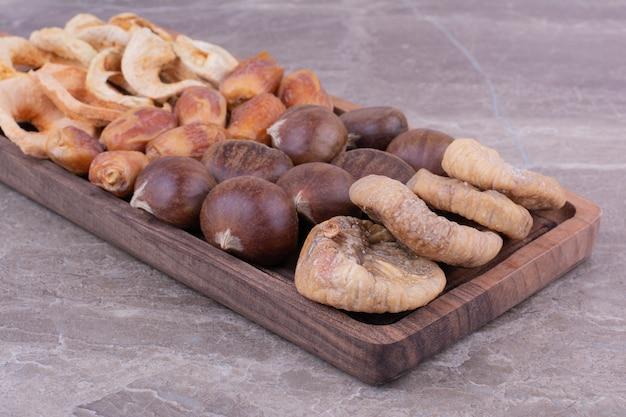 Frutas secas em uma travessa de madeira na pedra Foto gratuita