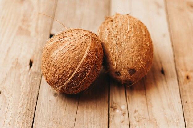 Frutas tropicais de coco em uma mesa de madeira em estilo rústico. Foto Premium
