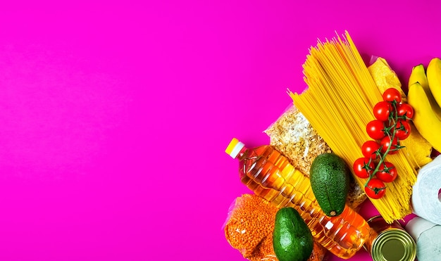 Frutas, vegetais, cereais, papel higiênico em uma superfície rosa Foto gratuita