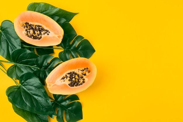 Fruto da papaia pela metade com folhas artificiais verdes sobre fundo amarelo Foto gratuita
