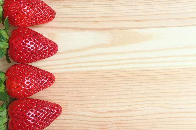 Frutos de morango maduro fresco vermelho vibrante alinhados na mesa de madeira Foto Premium