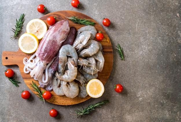 Frutos do mar frescos crus (camarões, lulas) na placa de madeira Foto Premium