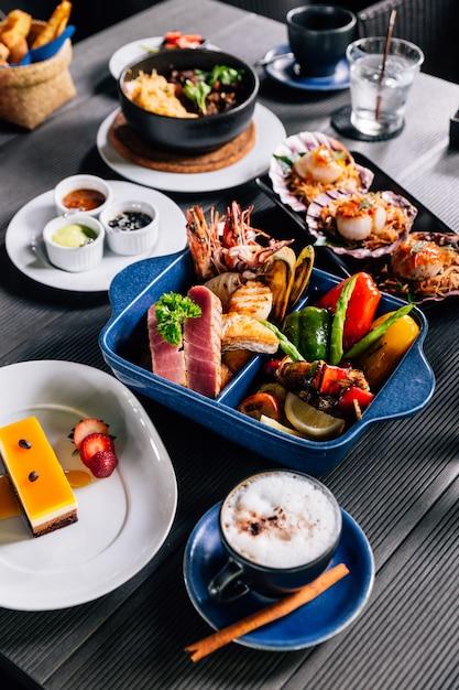 Frutos do mar misturados grelhados como peixe, lula, camarão, mexilhões e legumes. Foto Premium
