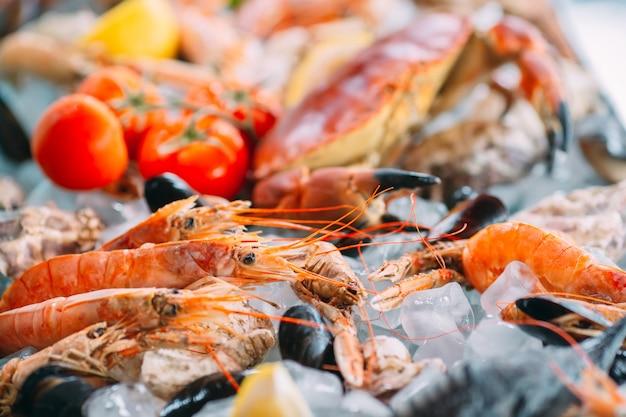 Frutos do mar no gelo. caranguejos, esturjão, marisco, camarão, rapana, dorado, em gelo branco. Foto Premium