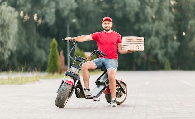 Full shot delivery guy em motocicleta com pedido Foto gratuita