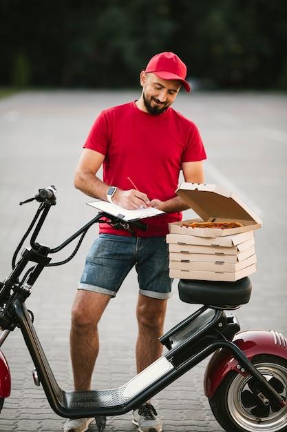 Full shot delivery guy escrevendo na área de transferência Foto gratuita