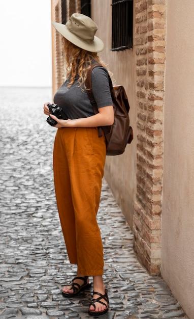 Full shot mulher com chapéu e câmera Foto gratuita