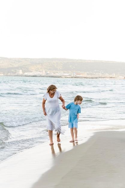 Full shot mulher e criança na praia Foto gratuita