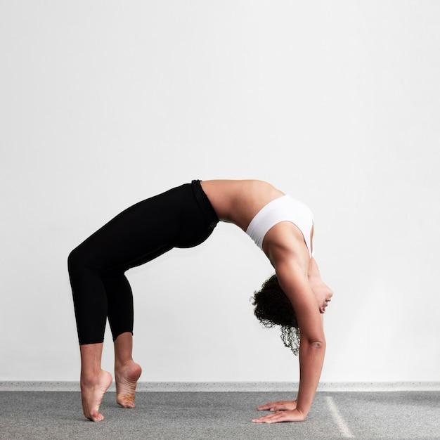 Full shot mulher fazendo um exercício complexo de ginástica Foto gratuita