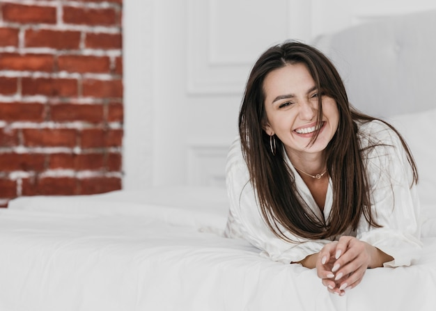 Full shot mulher feliz na cama Foto gratuita