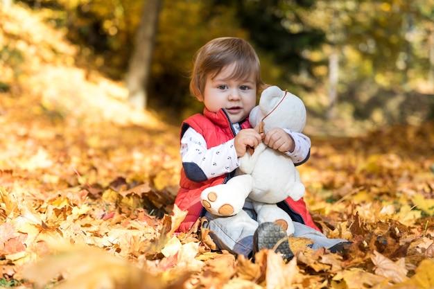 Full shot pequeno bebê abraçando brinquedo Foto gratuita