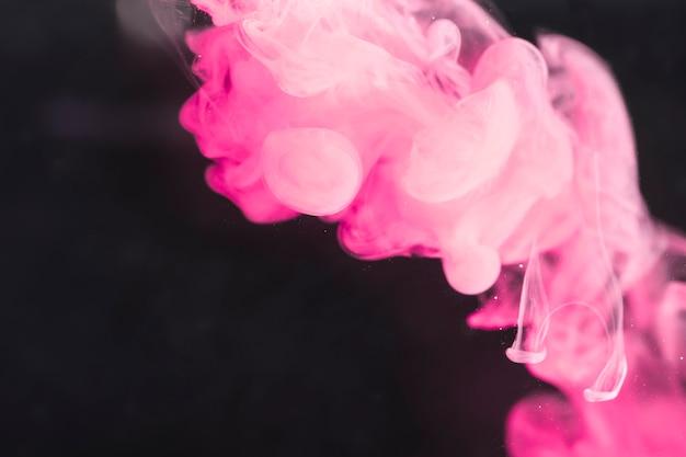 Fumaça artística poderosa rosa na tela preta Foto gratuita