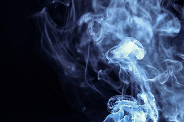 Fumaça azul abstrata isolada no fundo preto Foto Premium