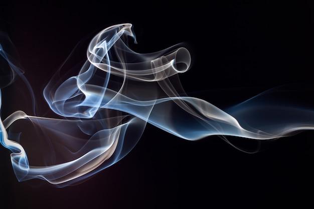 Fumaça azul e branca em fundo preto Foto Premium