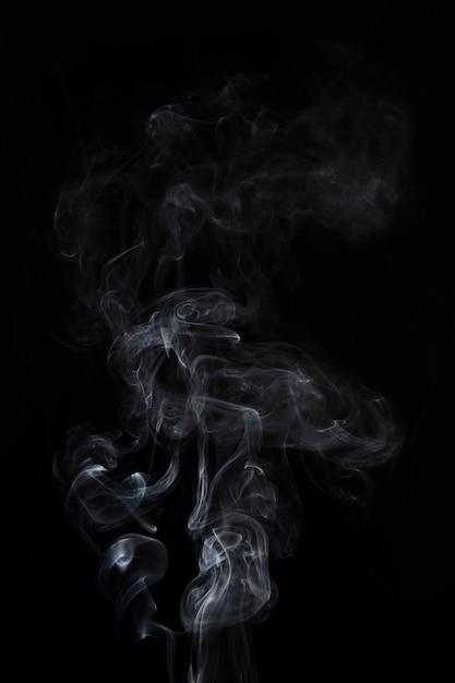 Fumaça branca abstrata redemoinhos em fundo preto Foto gratuita