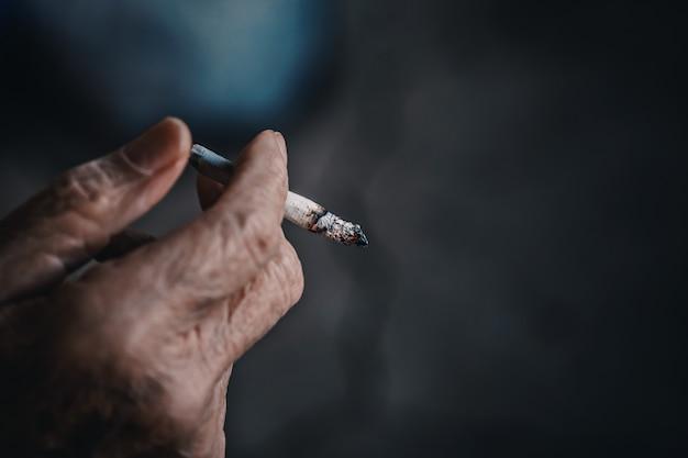 Fumando cigarro na mão de um homem velho. dependência de nicotina. Foto Premium