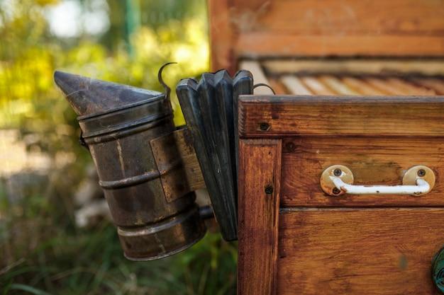 Fumante de abelha instalado na colméia de madeira. tecnologia de fumigação de abelhas. fumaça intoxicante para produção segura de mel. Foto Premium