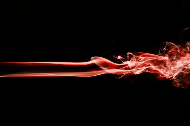 Fumo ondulado vermelho no fundo preto Foto gratuita