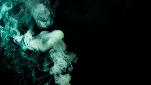 Fumo verde abstrato mover-se em fundo preto Foto gratuita