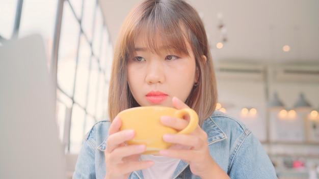 Funcionamento asiático autônomo da mulher do negócio, fazendo projetos no portátil e bebendo a xícara de café morna ao sentar-se na tabela no café. Foto gratuita