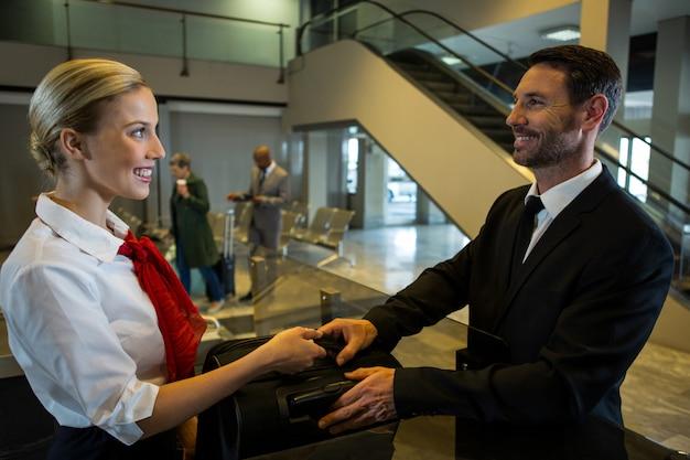 Funcionária entregando bagagem ao empresário Foto gratuita
