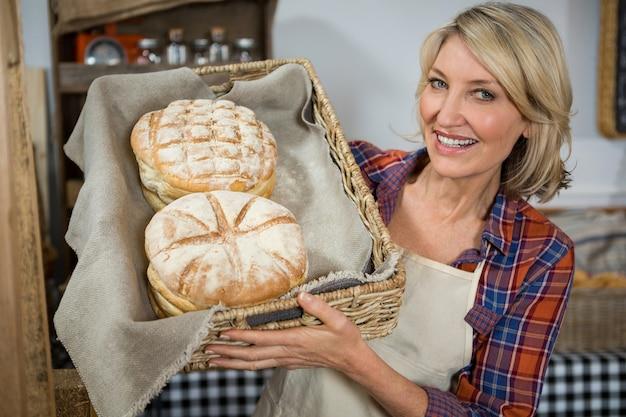 Funcionária feminina sorridente segurando uma cesta de pães de vime no balcão Foto Premium