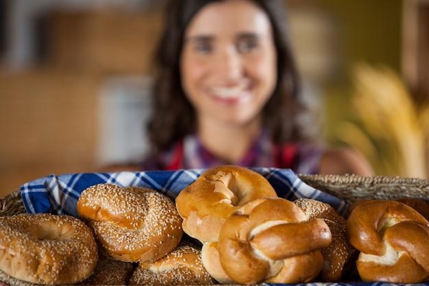 Funcionária feminina sorridente segurando uma cesta de vime com vários pães no balcão Foto Premium
