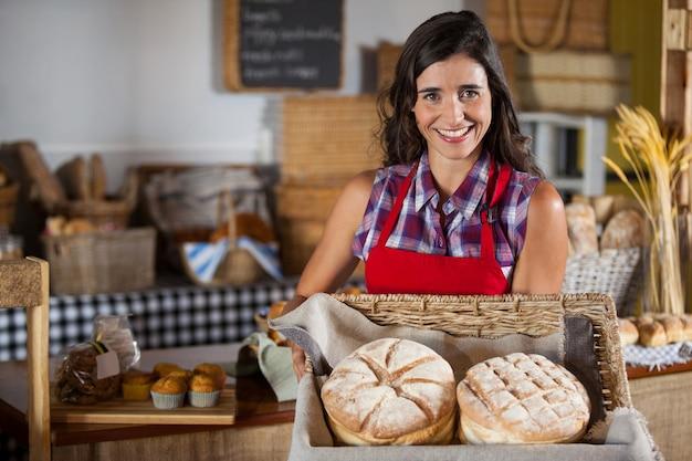 Funcionária sorridente segurando uma cesta de pães de vime no balcão Foto Premium