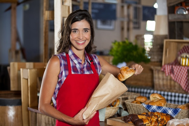 Funcionárias sorrindo embalando comida doce em um saco de papel no balcão de uma padaria Foto Premium