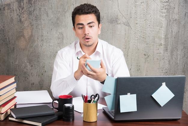 Funcionário chocado brincando com o telefone na mesa do escritório. Foto gratuita