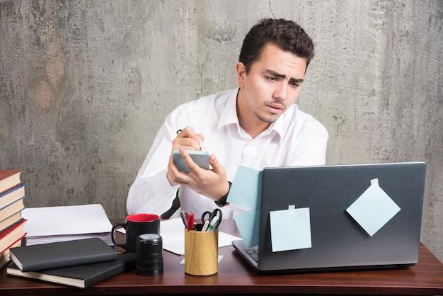 Funcionário de escritório olhando para o laptop e segurando o telefone na mesa do escritório. Foto gratuita