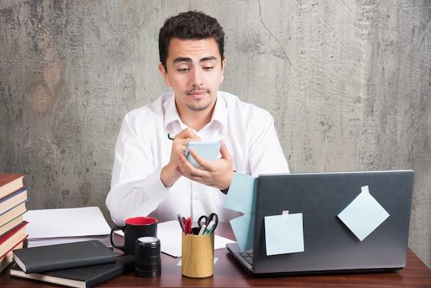 Funcionário de escritório olhando para o telefone na mesa do escritório. Foto gratuita