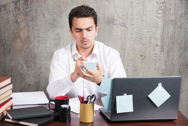 Funcionário do escritório olhando com raiva para o telefone na mesa do escritório. Foto gratuita